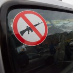 Humanitarian sign on car window, no guns, no weapons are carried in this vehicle