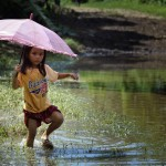 The day after Typhoon Bopha raged through the southern Philippines island of Mindanao, a girl in the village of Maasin wades through a flooded area. The ACT Alliance helped people in this village to recover from the 2011 passage of Typhoon Washi, and thus resist their vulnerability to Typhoon Bopha.