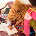A health care worker notes symptoms of a child suffering illness following floods in Pakistan. CWS-PA runs a mobile health clinic that sends doctors and health care workers to emergency-hit regions. Photo: ACT/CWS-PA/Khalid Rasheed