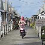 A woman rides a motorbike through Kuala Bubon, in Indonesia's Aceh province. The community of 118 houses was built by the ACT Alliance after the village's tsunami survivors refused to accept government plans to relocate them inland far from the sea. After the houses were built, the community then successfully fought a government plan to demolish part of the new village to make way for a new highway.