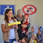 "Along with ensuring better access to clean water, IOCC hygiene educators also meet with refugee mothers and children regularly to share basic health tips.  ""Change your undergarments daily, wash well with soap and water, and hang to dry in the sun to kill germs"" is the written message that an IOCC hygiene promotion field officer shares on this day with the Syrian refugees.  Photo: Tiziana Cauli/IOCC"