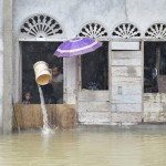A man pours flood water out of his house during November 2014 flooding in Meulaboh in Indonesia's Aceh province. Flooding in the region has grown worse because of climate change and the proliferation of palm oil plantations