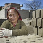 A woman rests from stacking cement blocks in Sanogoan, Nepal, that they and their neighbors will use to build new homes. This Newar community was hard hit by the April 2015 earthquake that ravaged Nepal, losing almost all their housing, but they've been helped by the Lutheran World Federation, a member of the ACT Alliance, to rebuild their lives. The ACT Alliance has provided a variety of services here since the quake, including blankets, tents, and livelihood assistance, and is helping villagers form the tens of thousands of cement blocks they will need to construct permanent housing.