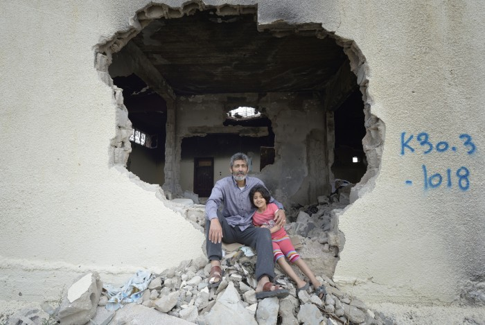 Fawzi Abu Jame'a, with his 7-year old daughter Raghad, sit in the ruins of what was once his parents' home Khan Yunis, Gaza. Houses in the area were destroyed by Israeli air strikes during the 2014 war between the state of Israel and the Hamas government of Gaza.