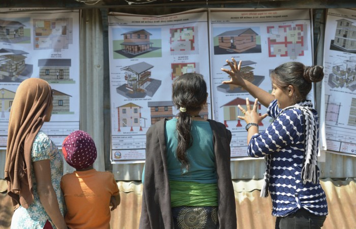 A volunteer for ACT Alliance member DanChurchAid explains to neighbours their options for constructing houses to replace the homes they lost in the 2015 Nepal earthquake. Photo Credit: ACT/Paul Jeffrey