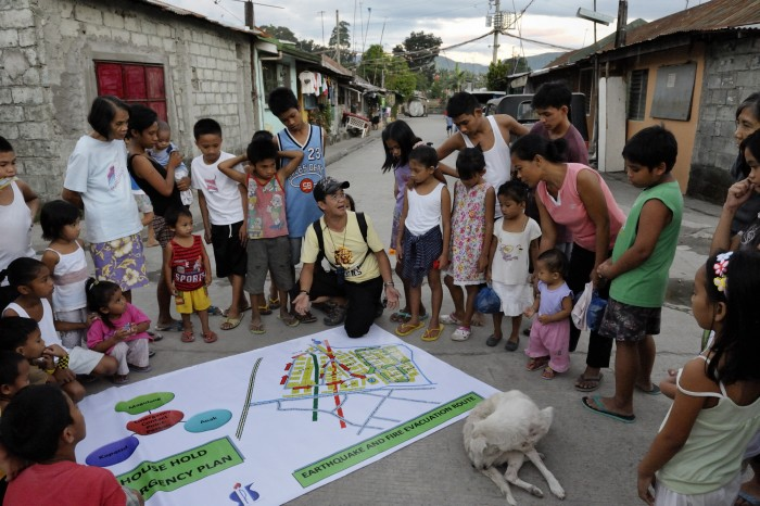 Jun Beltran, the executive secretary of the local homeowners' association, reviews a disaster risk reduction map with other residents in the Suburban neighborhood of Rodriguez, Rizal, in the Philippines. Most of the community's families were relocated here from other area of Manila and the nearby countryside to make way for urban renewal projects or to move them out of harm's way. Yet the new community was hit hard by Typhoon Ketsana in 2009, and Christian Aid, a member of the ACT Alliance, provided emergency relief supplies. Over the years since, with help from Christian Aid and other groups, community members have organized themselves and engaged in a process of disaster risk reduction, including identifying and mapping high-risk zones and evacuation routes in their area. Christian Aid has also assisted with financial and technical support for income generating livelihood projects and community enterprises. Photo: Paul Jeffrey