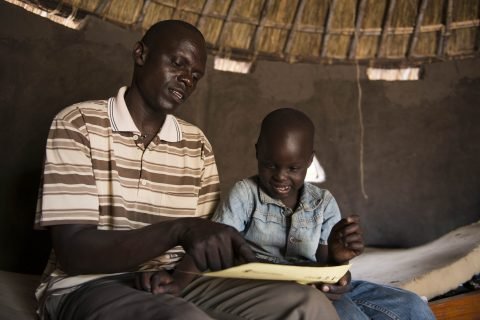 Thesame and his father John inside their tuku at a refugee settlement in Adjumani. Photo: Hugh Rutherford /Finn Church Aid.