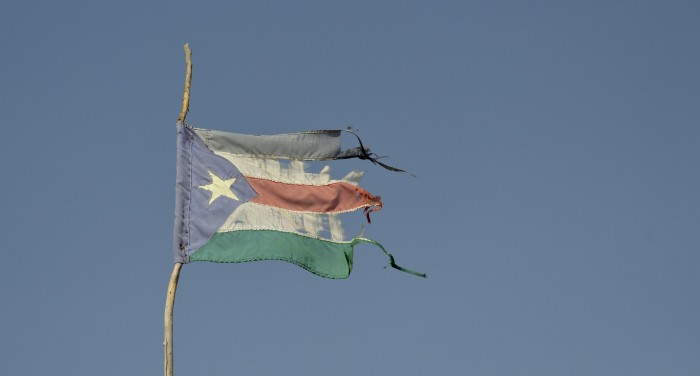 The flag of South Sudan, a little worse for wear, flies over the market in the town of Alek. Photo: Paul Jeffrey