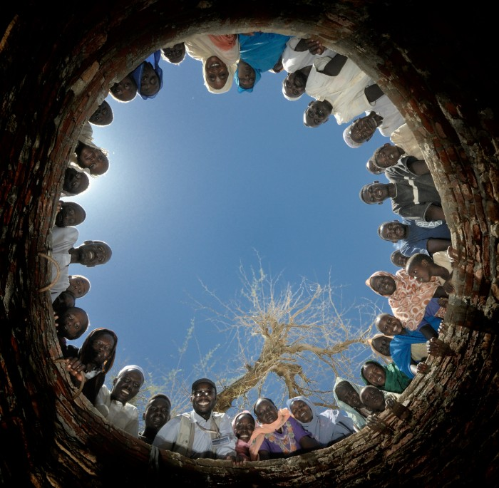 It takes a village to build a well. Residents of the Khamsadegaig Camp for internally displaced persons look down a well they built with help from the Darfur Emergency Response Operation, a joint program of Caritas Internationalis and ACT Alliance. The Catholic and Protestant aid networks have pooled their resources since 2004 in order to help some of the 2.5 million people displaced by violent conflict in Sudan's western Darfur region. Photo: Paul Jeffrey