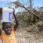 Ein Junge hat Wasser fuer die Familie an einer Wasserversorgung durch Norwegian Church Aid (NCA)  in einem kleinen Dorf nahe Les Cayes am 14.10.16 geholt. Foto: Thomas Lohnes fuer Diakonie Katastrophenhilfe
