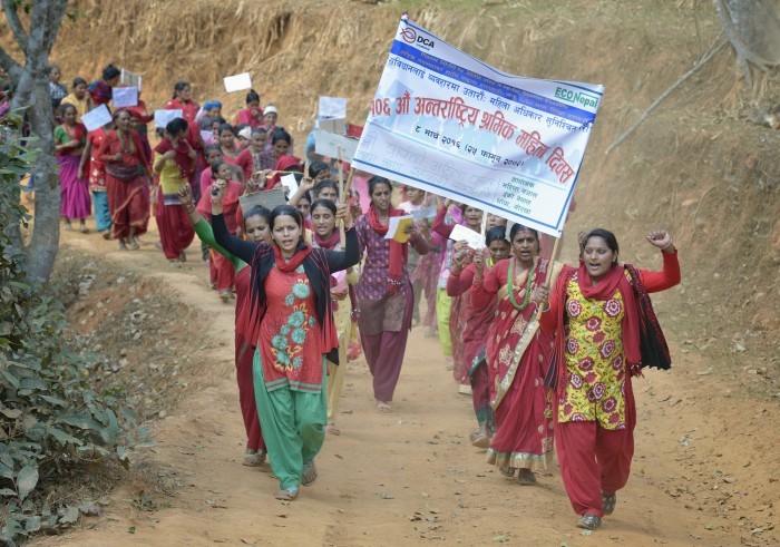 "Women march together in celebration of International Women's Day on March 8, 2016, in Dhawa, a village in the Gorkha District of Nepal. The banner reads, ""106th International Women's Day"" and ""Implement the Constitution and Guarantee Women's Rights."" Photo: Paul Jeffrey"