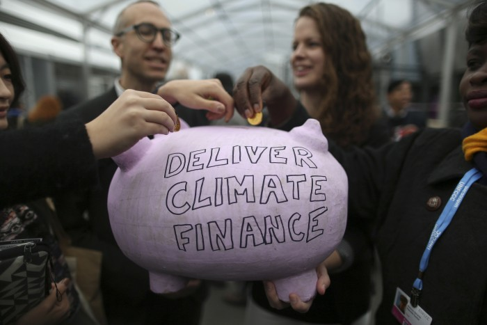 Participants contribute coins into a piggy bank during the World Climate Change Conference 2015 (COP21) at Le Bourget, near Paris, France, December 10, 2015. REUTERS/Stephane Mahe