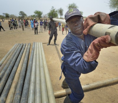 Workers carry pipe as they drill a well on April 7, 2017, in Rumading, a village in South Sudan's Lol State where more than 5,000 people, displaced by drought and conflict, remain in limbo. In early 2017, they set out walking for Sudan, seeking better conditions, but were stopped from crossing the border. They remain camped out under the trees at Rumading, eating wild leaves as the rainy season approaches. In early April, Norwegian Church Aid, a member of the ACT Alliance, began drilling the well in the informal settlement and distributed sorghum, beans and cooking oil to the most vulnerable families. The ACT Alliance is carrying out the emergency assistance in coordination with government officials and the local Catholic parish. South Sudan. Photo: Paul Jeffrey/ACT
