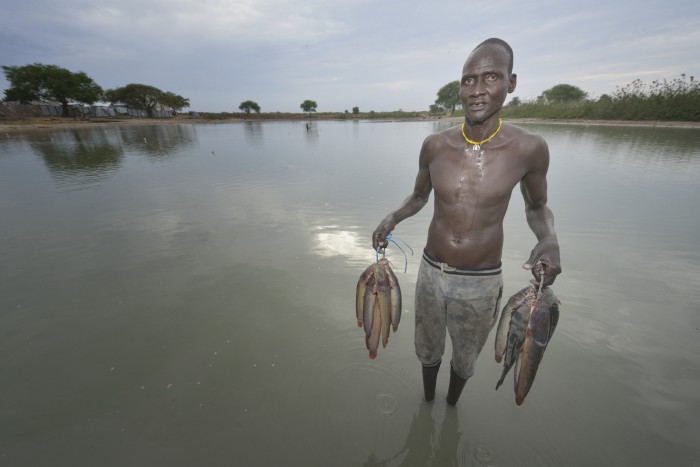 Mobil Kon displays fish he caught in Poktap, a town in South Sudan's Jonglei State where conflict, drought and inflation have caused severe food insecurity. The Lutheran World Federation, a member of the ACT Alliance, is helping families tackle food problems, including by providing cash for the purchase of fishing line and hooks. South Sudan. Photo: Paul Jeffrey/ACT