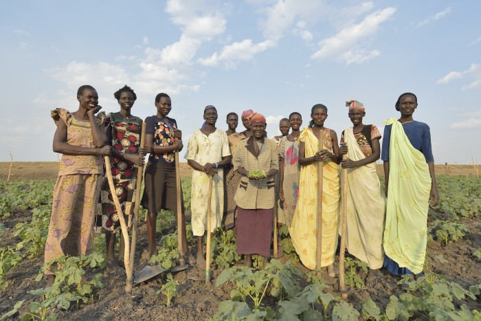 Women pose together after working in a community vegetable garden, in Dong Boma, a Dinka village in South Sudan's Jonglei State. Most of the women's families face serious challenges in rebuilding their village while simultaneously coping with a drought which has devastated their cattle herds. Credit: Paul Jeffrey