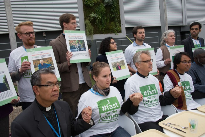 An interfaith group of religious leaders sits in front of empty trays during a public action at COP21 in Paris in 2015.  Photo: Ryan Rodrick Beiler/LWF