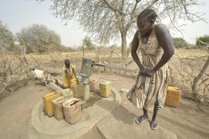 A mother and daughter draw water from a well with a hand pump in South Sudan. Photo: Paul Jeffrey/ACT