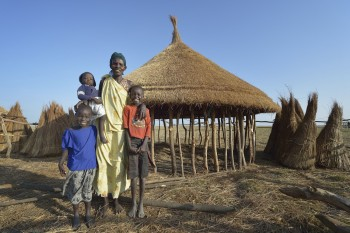 Adhieu Deng Ngewei and three of her children pose in front of their new hut on April 12, 2017, in Dong Boma, a Dinka village in South Sudan's Jonglei State. They and most other families here recently returned home after being displaced by rebel soldiers in December, 2013, and they face serious challenges in rebuilding their village while simultaneously coping with a drought which has devastated their cattle herds. During the period they were displaced, this family took refuge on an island of the White Nile River, living on the edge of starvation for almost three years. The Lutheran World Federation, a member of the ACT Alliance, is helping the villagers restart their lives with support for housing, livelihood, and food security. The ACT Alliance funded the construction of this family's new hut. South Sudan