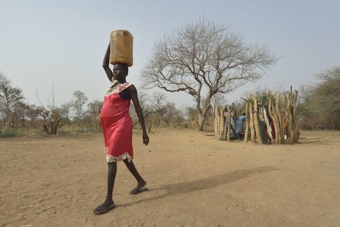 Mary Kuol carries water home from a well dug by the ACT Alliance in Yang Kuel, a village in South Sudan's Lol State - Credit: Paul Jeffrey