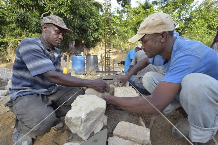 Ernst Beouchamp (left) and Saintorick Joseph place stones in the foundation of a house being built by Church World Service for a family that lost their home in Lareserve, a village near Jean-Rabel in northwestern Haiti, during Hurricane Matthew in 2016. Photo: Paul Jeffrey