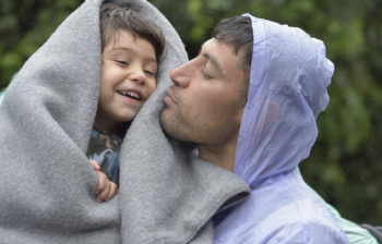 Refugees on their way to western Europe, a man from Iran holds his son as they approach the border into Croatia near the Serbian village of Berkasovo. The ACT Alliance has provided critical support for refugee and migrant families here and in other places along their journey.