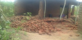 A house with fallen walls; a family is still using the remaining room