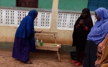 A parent teaches other parents how to use hand sanitizer after being trained by FCA. Photo: Mohamed Ibrahim/FCA Somalia