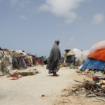 woman and tents in a refugee camp near Mogadishu